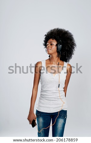 Happy african woman with afro and casual clothing dancing to the music she is listening to on her phone - stock photo