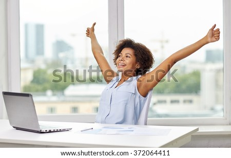 happy african woman with laptop at office - stock photo