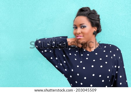 Happy African woman with makeup and hair style updo with braids and copy space - stock photo