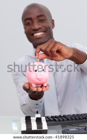 Happy Afro-American businessman saving money in a piggybank in the office