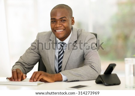happy afro american businessman using computer in office - stock photo