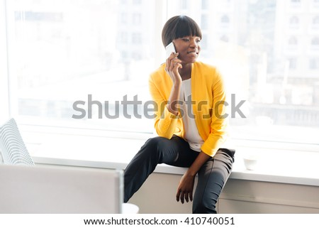 Happy afro american businesswoman talking on the phone in office - stock photo