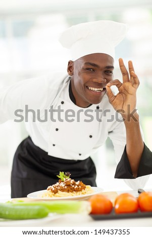 happy afro American chef in white uniform making delicious hand sign - stock photo
