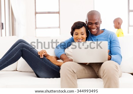 happy afro american couple using laptop at home with their son on background