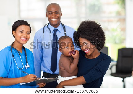 happy afro american mother holding her baby boy after checkup with nurse and doctor - stock photo
