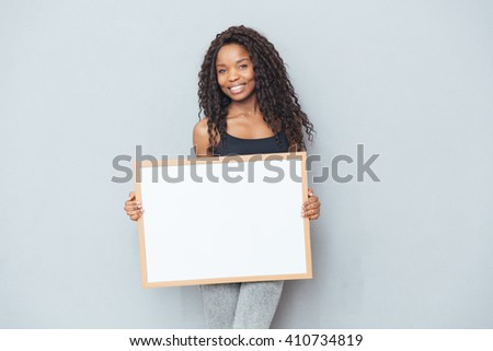 Happy afro american woman showing blank board over gray background - stock photo