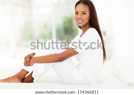 happy afro american woman sitting on bed at home - stock photo