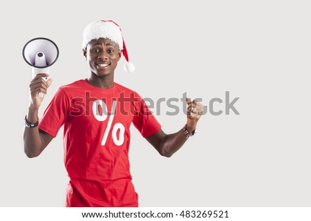 Happy Afro man with by megaphone wearing a Santa hat