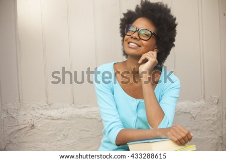 Happy afro woman with books and glasses - stock photo