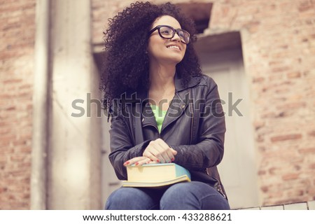 Happy afro woman with books and glasses
