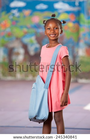 Happy afroamerican female student in elementary schoolyard. - stock photo