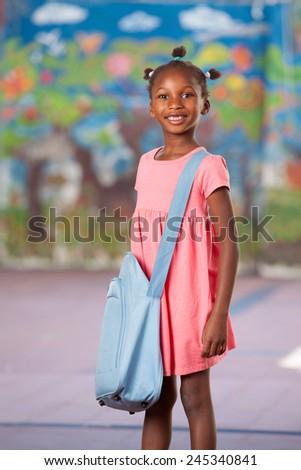 Happy afroamerican female student in elementary schoolyard. - stock photo