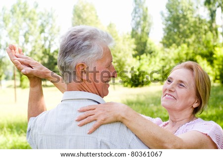 happy aged couple dancing at the nature - stock photo