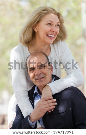 Happy aged heterosexual couple with smiles holding hands of each other outdoor