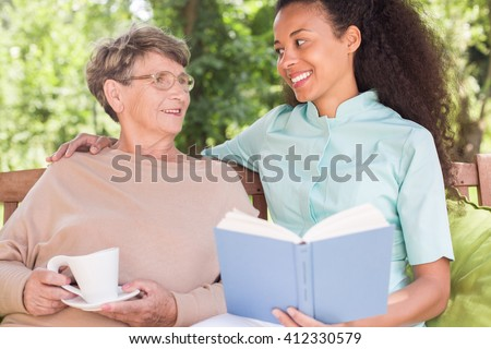 Happy aged woman and young nurse spending afternoon together - stock photo