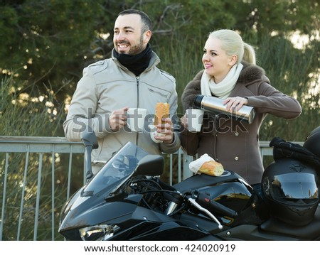 happy american couple posing near motor bike with sandwitches and coffee - stock photo