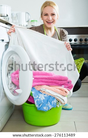 Happy american  housewife using washing machine at home