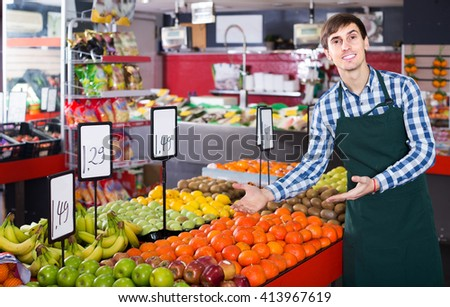 happy american male seller posing with apples, tangerines and bananas in store
