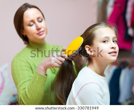 Happy american woman sitting on couch and combing girl hair - stock photo
