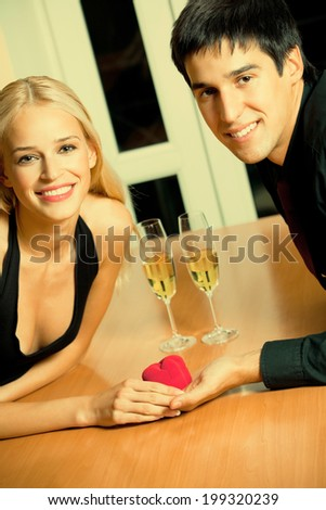 Happy amorous couple and a special man proposal in restaurant - stock photo