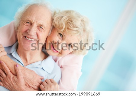 Happy and affectionate elderly couple looking at camera - stock photo