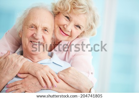 Happy and affectionate elderly couple posing for camera - stock photo