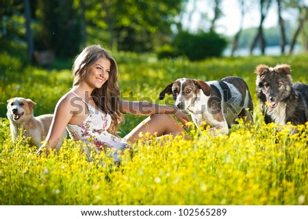 Happy and attractive teen girl playing with dogs in green field - stock photo