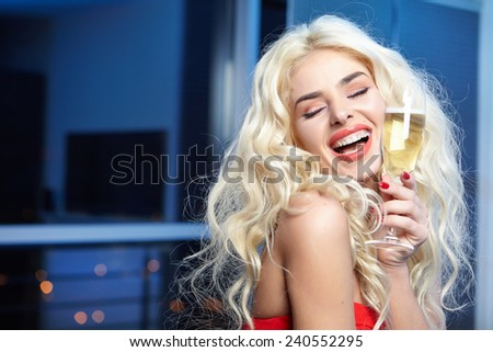 Happy and beautiful blond woman in a party red dress with a glass of champagne  - stock photo