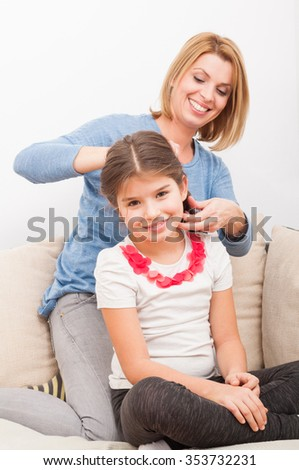 Happy and beautiful mother and daughter at home on the couch or sofa