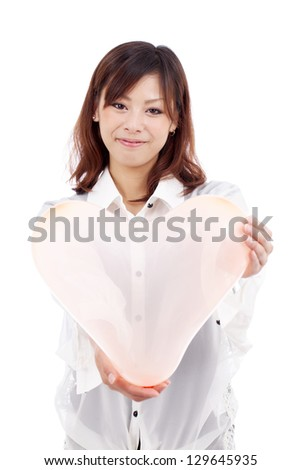 Happy and beautiful young asian girl holding a pink heart shaped balloon, isolated on white background