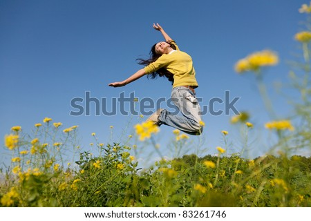 Happy and beautiful young girl jumping high in a summer field - stock photo
