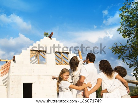 Happy and big family builds a new house for living - stock photo