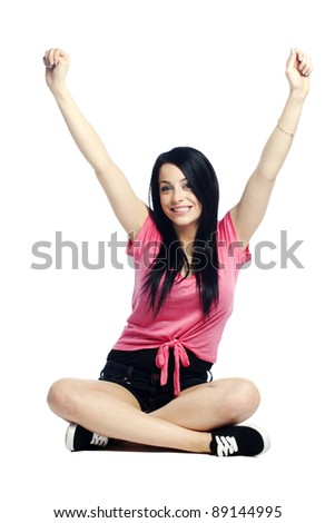 Happy and calm young woman sitting cross legged thrilled and excited - stock photo