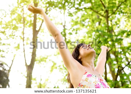 Happy and carefree woman raising arms  to the sky on fresh bright spring greenery. Caucasian beautiful girl happiness and relaxation on nature. - stock photo