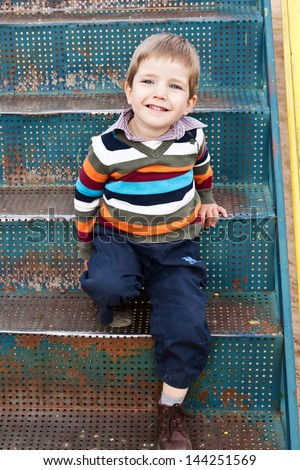 Happy and cheerful boy playing on the playground