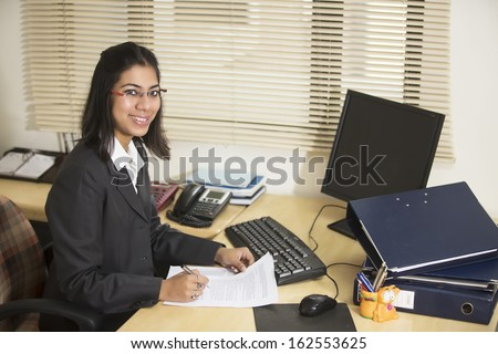 Happy and cheerful Business woman at her workstation. - stock photo