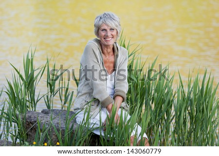 Happy and cheerful old lady sitting near the lake and enjoying the views. - stock photo