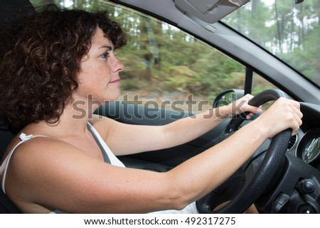 Happy and cheerful woman driving a car