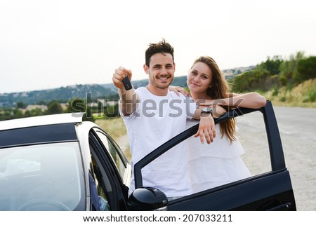 happy and cheerful young couple driving new car during holiday trip in summertime in countryside