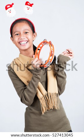 Happy and cheerful young lady with a tambourine singing christmas carol.
