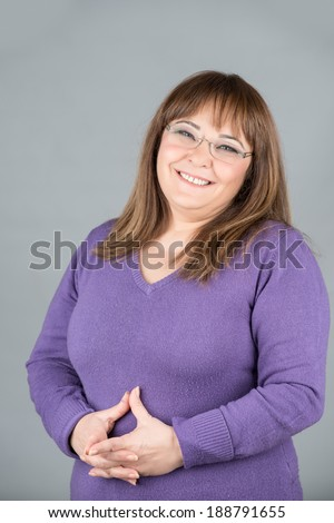 Happy and chubby woman with glasses smiling - stock photo