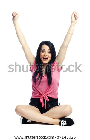 Happy and confident young woman excited with arms up smiling - stock photo