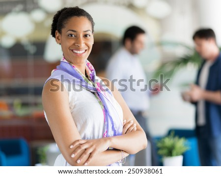 Happy and confident young woman in an office - stock photo