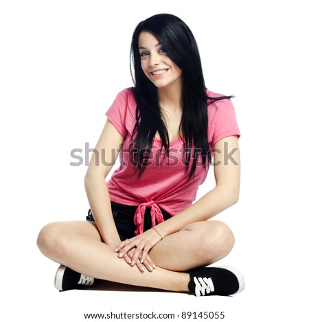 Happy and confident young woman sitting cross legged smiling - stock photo