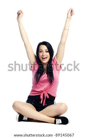 Happy and confident young woman sitting cross legged smiling with arms up - stock photo