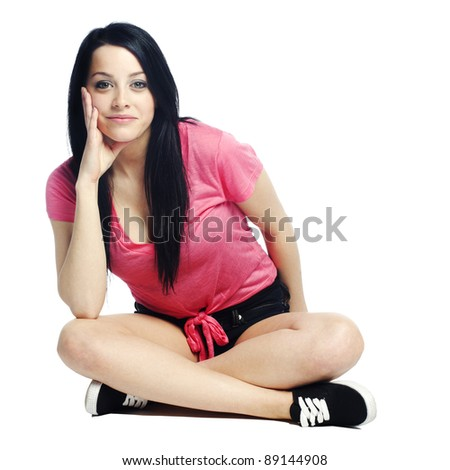 Happy and confident young woman sitting down dressed for summer - stock photo