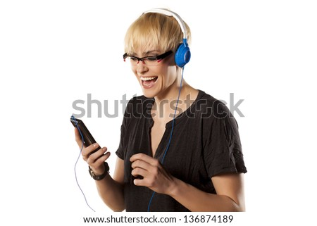 happy and cute short haired blonde plays with headphones and music from her phone