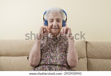 happy and energetic senior woman listening music with headphones - stock photo