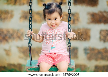 Happy and enjoy concept picture of 1 year 9 months baby playing a swing in the playground : Selective focus. - stock photo