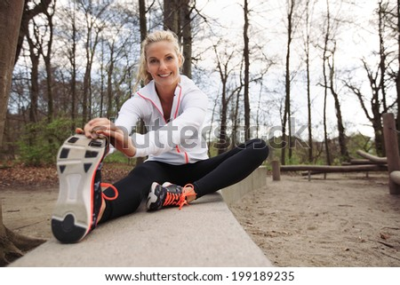 Happy and fit woman stretching her legs before training session in nature. Beautiful caucasian athlete exercising at the park smiling at camera. - stock photo